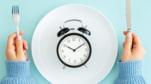2 hands holding a knife and a fork combining with a white plate and a clock on top | Feature | 10 Reasons Why Intermittent Fasting Is The Simplest Diet Ever
