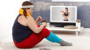 an overweight girl wearing sport cloth and eating cake while watching fitness show | Feature | Why Can't I Lose Weight!? | 6 Stubborn Weight Loss FAQs