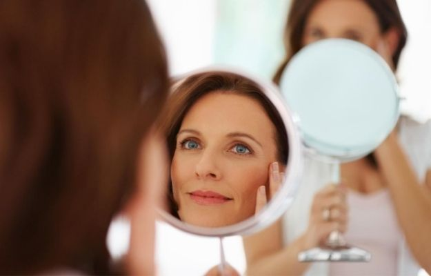 a woman happily looking into the mirror | 5 Ultherapy Benefits For Looking Younger