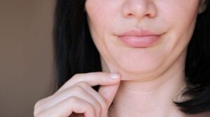 a woman is peeling her chin skin | Feature | 7 Different Saggy Skin Solutions
