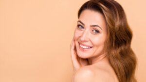a women is smiling and touching her cheek | Feature | 5 Ultherapy Benefits For Looking Younger