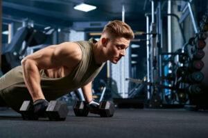 Muscular man doing push ups using dumbbells.
