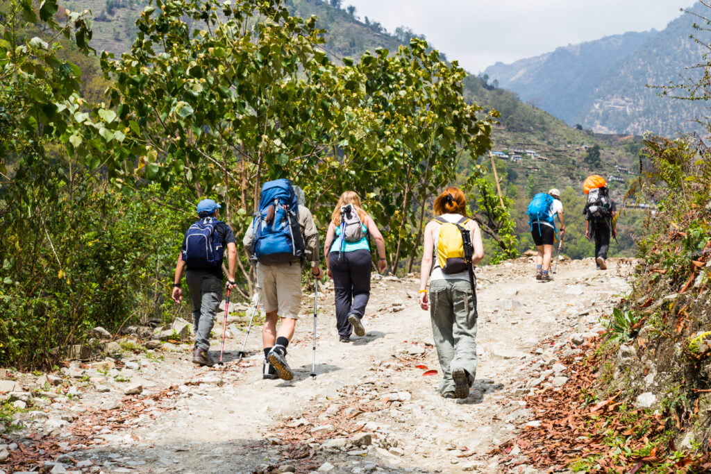 a-group-of-people-trekking-on-dirt-road-in-nepal-PFYBHTS